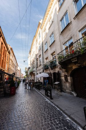 Photo for LVIV, UKRAINE - OCTOBER 23, 2019: street cafe and people walking along narrow street in city center - Royalty Free Image