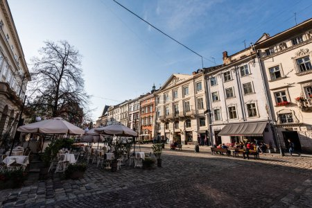 Photo for LVIV, UKRAINE - OCTOBER 23, 2019: people sitting in street cafe near old houses in city center - Royalty Free Image