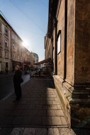Photo for LVIV, UKRAINE - OCTOBER 23, 2019: man standing on street and old houses against blue sky with bright sun - Royalty Free Image