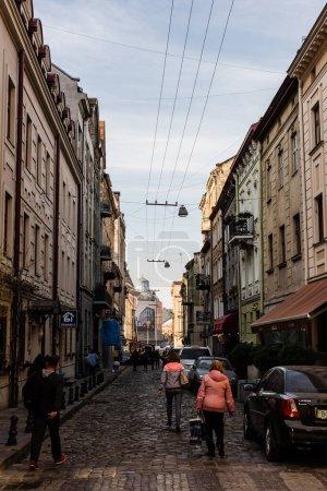 Photo pour LVIV, UKRAINE - 23 OCTOBRE 2019 : voitures stationnées et personnes marchant près de la maison avec lettrage cyrillique sur l'enseigne - image libre de droit