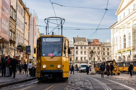 Photo for LVIV, UKRAINE - OCTOBER 23, 2019: tram with route number one lettering and people walking along street in city center - Royalty Free Image