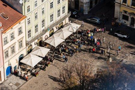 Photo pour LVIV, UKRAINE - 23 OCTOBRE 2019 : vue aérienne de personnes marchant près d'un café de rue sur la place du marché - image libre de droit