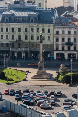 Photo for LVIV, UKRAINE - OCTOBER 23, 2019: aerial view of Adam Mickiewicz Monument near car parking and authentic houses - Royalty Free Image