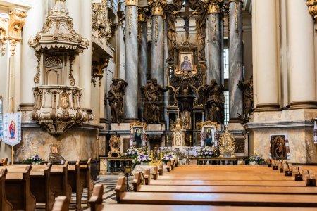 Foto de LVIV, UCRANIA - 23 DE OCTUBRE DE 2019: interior de la iglesia dominicana con elementos decorativos en bancos de madera y dorados - Imagen libre de derechos