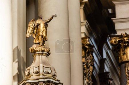 Photo pour LVIV, UKRAINE - 23 OCTOBRE 2019 : statue dorée d'archange tenant la bible à la main tendue dans une église dominicaine - image libre de droit