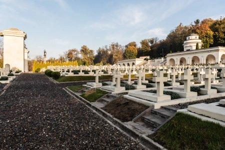 Photo pour LVIV, UKRAINE - 23 OCTOBRE 2019 : rangées de tombes polonaises avec croix près du chemin de gravier dans le cimetière lychakiv à lviv, ukraine - image libre de droit