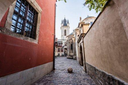 Photo pour Maison rouge près du mur du monastère et l'église de carmélite contre le ciel bleu à Lviv, ukraine - image libre de droit