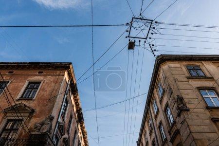 Photo pour Vue à angle bas des vieux bâtiments et des fils électriques contre le ciel bleu à lviv, ukraine - image libre de droit