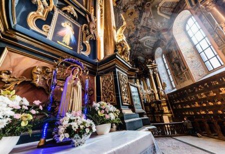 Foto de LVIV, UKRAINE - OCTUBRE 23, 2019: altar con nuestra estatua de dama, decorado con flores naturales en la iglesia carmelita. - Imagen libre de derechos