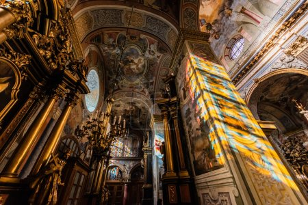 LVIV, UKRAINE - OCTOBER 23, 2019: low angle view of interior with paintings and gilded decoration in carmelite church