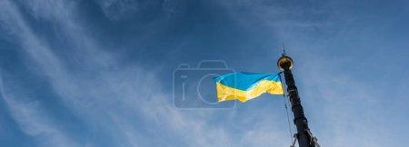 Photo pour Image horizontale du drapeau ukrainien sur le mât de drapeau contre le ciel bleu à lviv, ukraine - image libre de droit