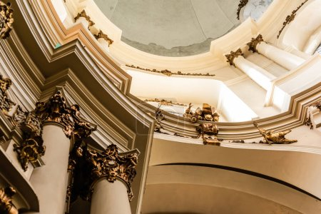 Photo pour LVIV, UKRAINE - 23 OCTOBRE 2019 : vue en angle bas des colonnes décorées avec des éléments dorés dans l'église dominicaine - image libre de droit