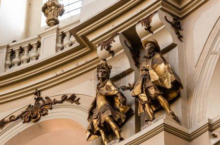 Foto de LVIV, UCRANIA - 23 de octubre de 2019: estatuas doradas masculinas en la iglesia dominicana cerca de arcos y balaustradas - Imagen libre de derechos