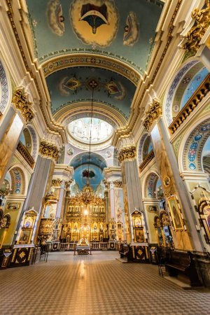 LVIV, UKRAINE - OCTOBER 23, 2019: interior of carmelite church with gilded altar, paintings on walls and tiled floor