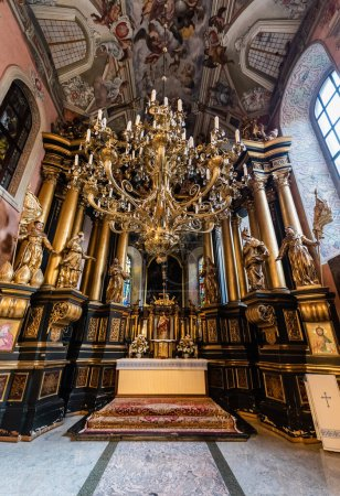 Photo pour LVIV, UKRAINE - 23 OCTOBRE 2019 : intérieur de l'église en carmélite avec colonnes dorées, statues et lustre - image libre de droit
