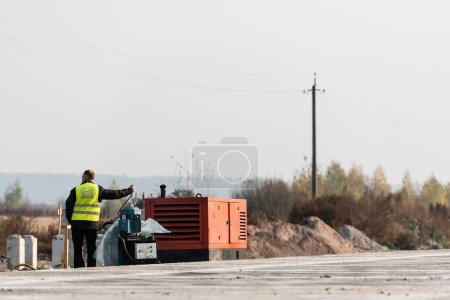 Photo for LVIV, UKRAINE - OCTOBER 23, 2019: back view of worker starting engine of generator during roadworks - Royalty Free Image