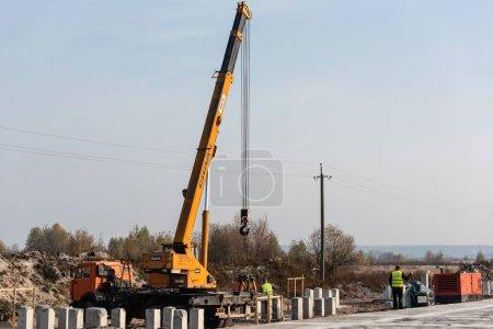 Photo pour LVIV, UKRAINE - 23 OCTOBRE 2019 : camion et grue avec lettrage en teck et inscription cyrillique, et blocs de béton près des travailleurs sur l'autoroute - image libre de droit