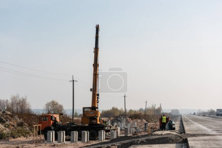 Photo for LVIV, UKRAINE - OCTOBER 23, 2019: truck with crane with dak lettering, and concrete blocks near workers on highway - Royalty Free Image