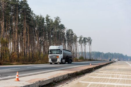 LVIV, UKRAINE - OCTOBER 23, 2019: truck with cistern and daf inscription moving on highway along trees