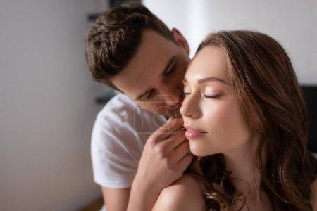 Selektiver Fokus eines gutaussehenden Mannes, der das Gesicht eines schönen Mädchens mit geschlossenen Augen berührt