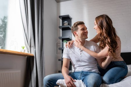 Photo for Cheerful couple looking at each other and smiling in bedroom - Royalty Free Image
