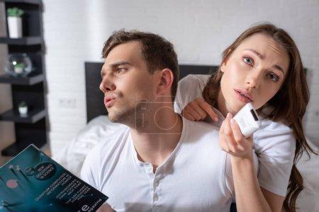 Photo pour Mécontent homme tenant magazine tout en se sentant chaud près de la femme avec télécommande de climatiseur - image libre de droit