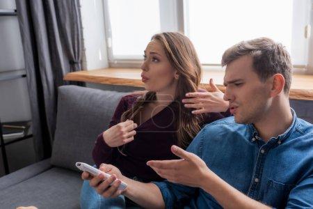 Photo pour Fille assise sur le canapé près de l'homme pointant avec la main à la télécommande du climatiseur tout en se sentant chaud - image libre de droit