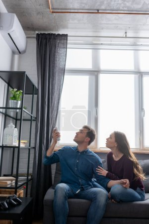 man and woman looking at air conditioner while sitting on sofa