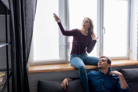 Photo pour Homme mécontent près de femme attrayante tenant télécommande de climatiseur tout en se sentant chaud - image libre de droit