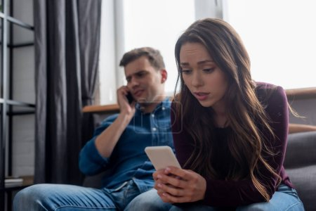 Photo for Selective focus of girl texting while holding smartphone and man talking in living room - Royalty Free Image