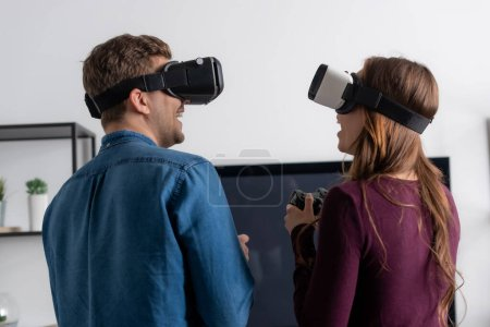 Photo for KYIV, UKRAINE - MAY 15, 2020: cheerful couple in virtual reality headsets playing video game in living room - Royalty Free Image