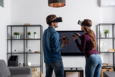 Photo for KYIV, UKRAINE - MAY 15, 2020: cheerful couple in virtual reality headsets holding joysticks and playing video game in living room - Royalty Free Image