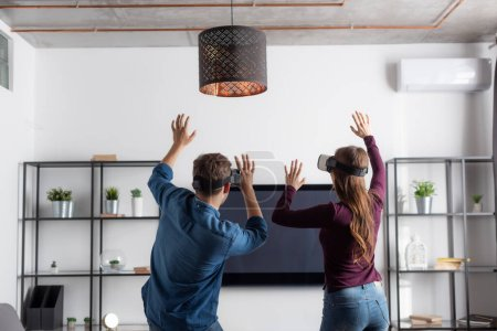 Photo pour Vue arrière du couple dans les casques de réalité virtuelle gesticulant tout en jouant dans le salon - image libre de droit
