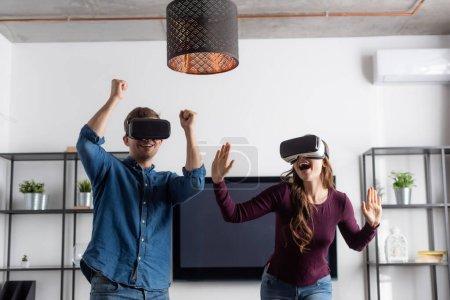 Photo pour Couple heureux dans les casques de réalité virtuelle célébrant triomphe tout en jouant dans le salon - image libre de droit