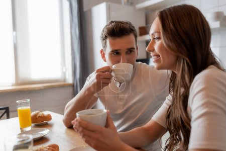 selective focus of man drinking coffee and looking at cheerful girlfriend in kitchen