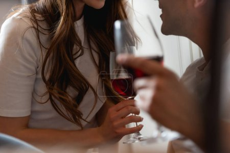 Photo for Cropped view of couple holding glasses of red wine - Royalty Free Image