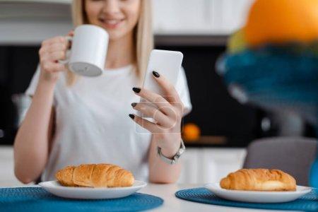Foto de Vista recortada de niña sosteniendo teléfono inteligente y taza cerca de croissants - Imagen libre de derechos