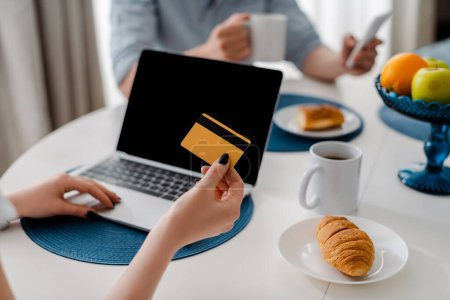 cropped view of girl holding credit card near laptop with blank screen and breakfast on table