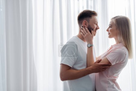 Photo pour Vue latérale de la fille avec bague de fiançailles sur le doigt touchant le visage du bel homme - image libre de droit