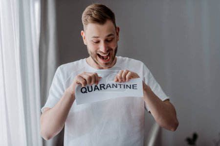 excited man ripping paper with quarantine lettering
