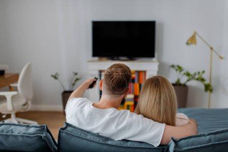 Photo pour Vue arrière de l'homme et de la femme assis près de la télévision à écran plat avec écran blanc - image libre de droit