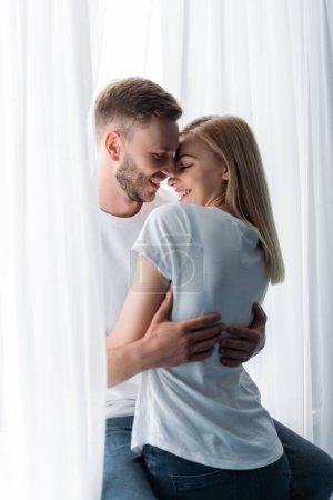 Photo pour Homme heureux et barbu embrassant petite amie attrayante - image libre de droit