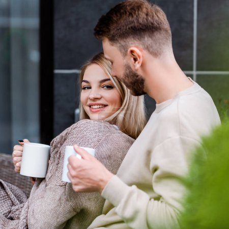 Photo for Selective focus of happy girl holding cup and looking at camera near bearded boyfriend - Royalty Free Image