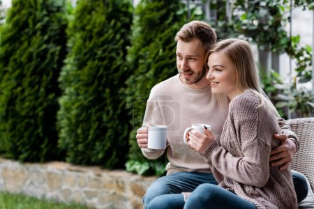 Photo for Handsome man and cheerful woman holding cups of tea and sitting outside - Royalty Free Image