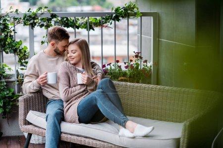 Photo pour Foyer sélectif de l'homme heureux et femme gaie tenant des tasses de thé et assis sur un canapé extérieur - image libre de droit