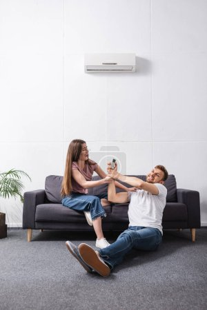 Photo for Young irritated couple with remote controller at home with broken air conditioner - Royalty Free Image