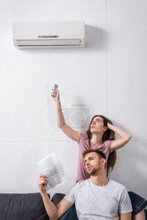 Photo pour Jeune couple avec télécommande et journal souffrant de chaleur tout en étant assis à la maison avec climatiseur cassé - image libre de droit