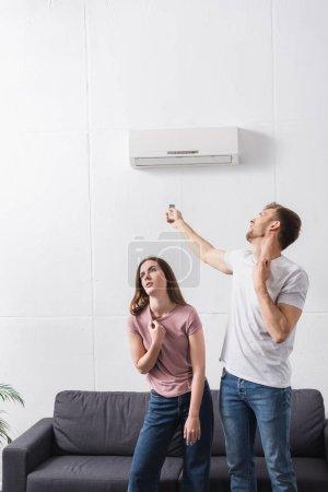 Photo pour Couple épuisé avec télécommande souffrant de chaleur à la maison avec climatiseur cassé - image libre de droit