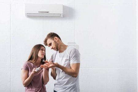 Photo pour Couple triste souffrant de chaleur à la maison avec climatiseur cassé - image libre de droit