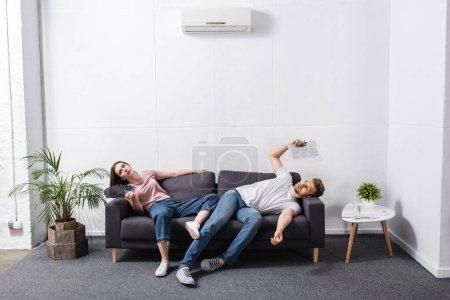 Photo pour Couple triste avec ventilateur à main et journal souffrant de chaleur à la maison avec climatiseur cassé - image libre de droit
